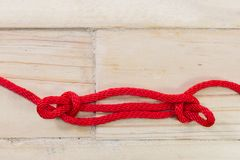 Sheepshank knot made with red rope on wooden background. Royalty Free Stock Image