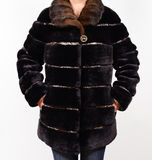 Sheepskin fur coat isolated on grey background. Fur coat on model without face. Outerwear. Fur coat. Stock Image