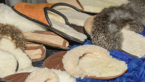 Sheepskin lined slippers on wool dyed in blue. Selective focus. Stock Photography
