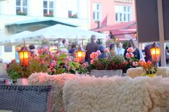 Pretty outdoor scene in the town square of Tallinn, Estonia. Sheepskin rugs hanging on the backs of the chairs are common here for outdoor cafe visitors to sit royalty free stock photography