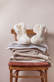 Sheepskin slippers, stack of warm clothes Stock Image