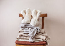Sheepskin slippers, stack of warm clothes Stock Photo