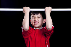 Sheer determination. A young boy is determined to do a pullup Stock Photos
