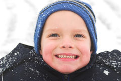 Sheer joy. A child smiles gleefully as he has the time of his life playing in the snow stock photography