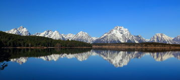 Mount Moran reflected in Jackson Lake, Grand Teton National Park, Wyoming. The sheer peaks of the Grand Teton Range and Mount Moran are reflected in the still royalty free stock image