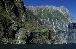 Sheer Rock and Mountain Coastline. Sheer rock walls and mountains create the coastline along Milford Sound and the Fiordland National Park, New Zealand Royalty Free Stock Photography