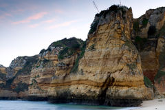 Sheer rocky cliffs. The sheer rocky cliffs at the beaches of 'Praia Dona Ana' in Lagos, Portugal, with a setting sunlit sky Stock Image