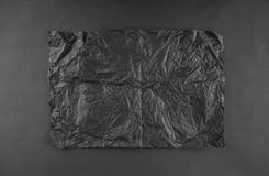 Sheet of black crumpled paper on black Stock Image
