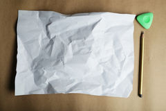 Sheet of blank paper and a pencil on brown background. Royalty Free Stock Images
