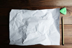 Sheet of blank paper and a pencil on brown wooden background. Stock Images