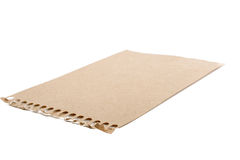 Sheet of brown torn notepaper. On a white background Stock Image