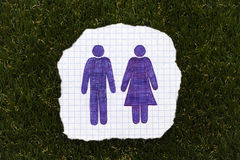 Sheet of checkered paper with hand drawn man and woman figures o Royalty Free Stock Photos