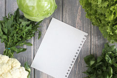 Sheet and composition of vegetables on grey wooden desk. Stock Image