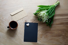 A sheet of dark paper, spring flowers, cup of coffee on a wooden texture Stock Image