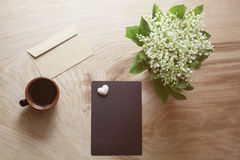 A sheet of dark paper, spring flowers, cup of coffee on a wooden texture Royalty Free Stock Images
