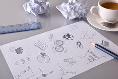 Sheet with drawings of relevant business concept on desk. Sheet with drawings of relevant business concept on gray office table with crumpled sheets and coffee Stock Photo