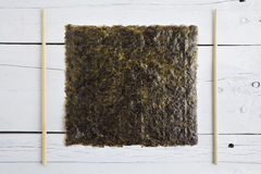 A sheet of dried seaweed and chopsticks Stock Photography