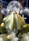 A sheet ghost in a night cemetery with Halloween pumpkins. royalty free stock photos