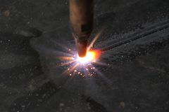 Sheet metal - gas cutting nozzle. Gas cutting nozzle cutting a thick MS sheet in a factory Stock Photos