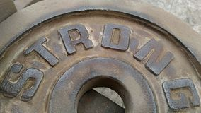 The Sheet metal with letters STRONG that are polisheding rust off. Stock Images