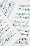 Sheet Music. Macro of three stained vintage music sheets Stock Image
