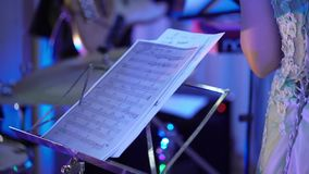 Sheet music, band at concert. Playing stock video