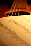 Sheet music on guitar 1 royalty free stock image