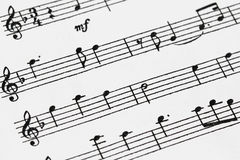 Sheet Music. Macro of  sheet music with treble clef, notes and with a designation volume mf (mezzo-forte) - moderately loud Royalty Free Stock Photos