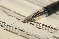 Sheet music and pen. An old music sheet and pen - focus on foreground Royalty Free Stock Images