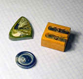 On a sheet of notebook pencil sharpener, a button and a stone amulet Stock Photography