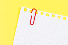 Sheet notepad paper clip on yellow background. Stock Images