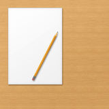 Sheet of office paper with yellow pencil on wooden background. Royalty Free Stock Photos