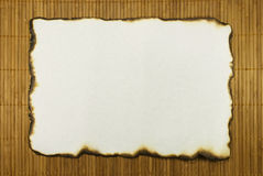 Sheet Of An Old Paper. The sheet of an old paper with burnt edges lays on a bamboo laying Stock Images