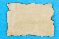 A sheet of old papyrus, Kraft paper. As a background on a blue table. Copy space for text Stock Photography