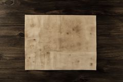 Sheet old vintage paper on the aged wooden background. Stock Photos