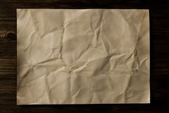 Sheet old vintage paper on the aged wooden background. Royalty Free Stock Images