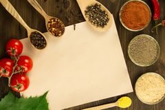 Sheet old vintage paper with spices on wooden background. Healthy vegetarian food. Recipe, menu Royalty Free Stock Photo