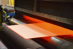 Sheet of orange-coloured material being fed through machine Stock Photos