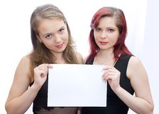 Sheet of paper. Two girls hold a sheet of paper Royalty Free Stock Image