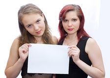 Sheet of paper. Two girls hold a sheet of paper Stock Photo