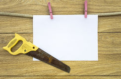 Sheet of paper on clothespins, old and rusty hand saw royalty free stock photography