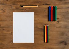 Sheet of paper, colored markers and pencils Royalty Free Stock Photos