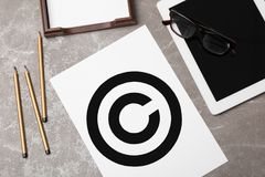 Sheet of paper with copyright symbol and tablet. On grey background. Law compliance concept stock image