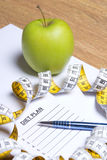 Sheet of paper with diet plan, apple, pen and measure tape Royalty Free Stock Photos
