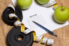 Sheet of paper with diet plan, apples and dumbbell Stock Photos