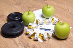 Sheet of paper with diet plan, apples, dumbbells and measure tap Royalty Free Stock Images