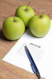 Sheet of paper with diet plan, pen and apples Stock Photo