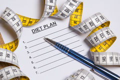 Sheet of paper with diet plan, pen and measure tape Royalty Free Stock Photography