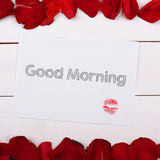 Sheet of paper Good Morning with a kiss. Note and rose petals on the table Stock Photos