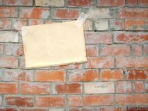 Sheet of a paper, hanging on a brick wall Royalty Free Stock Images